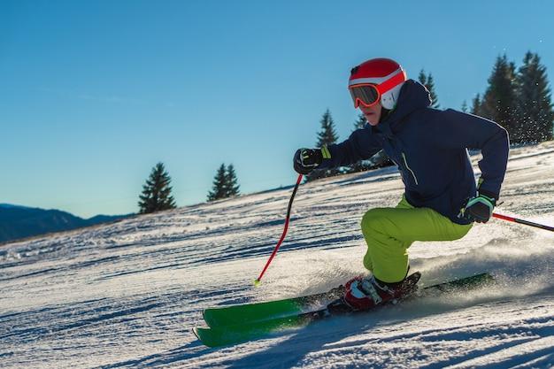 Weergave van een man met groene broek en fel oranje helm tijdens het skiën op een zonnige dag