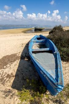 Weergave van een oude verlaten boot gestrand op droog zand op het strand.