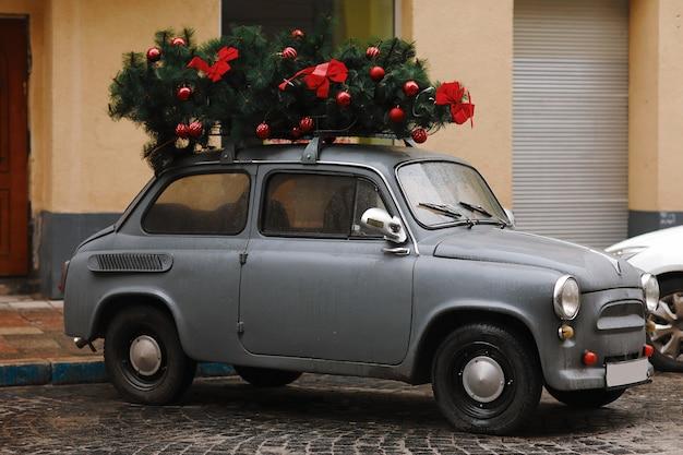 Weergave van een rode retro auto met kerstboom. winter. kerstmis.