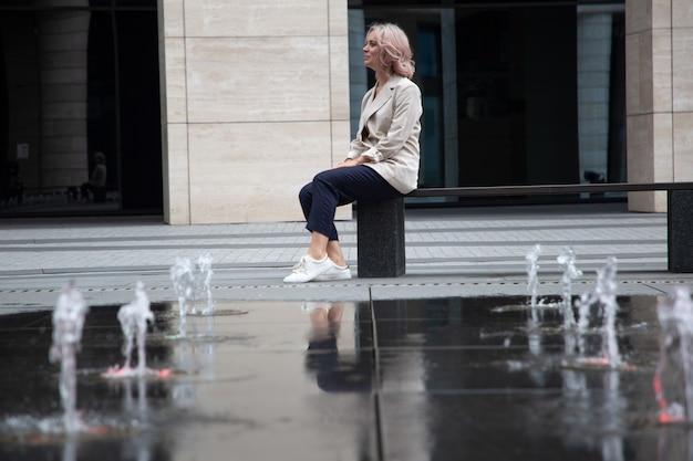 Weergave van een zakenmeisje dat tijdens de lunch bij de fontein rust