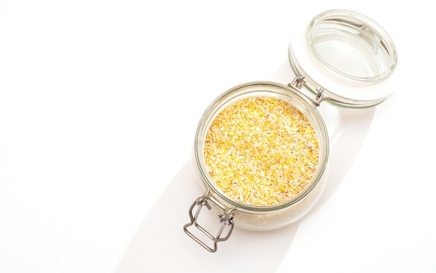 Weergave van gebroken tarwe gries in glazen pot close-up