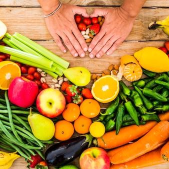 Weergave van gemengde groenten en fruit op een houten tafel en vrouwenhanden die een haardsymbool doen