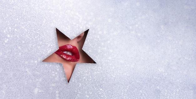 Weergave van heldere lippen met glitters door gat in zilver papier achtergrond.