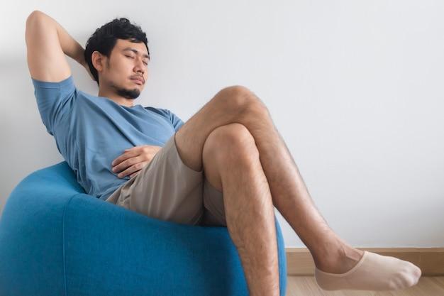 Weergave van iemands benen op wit bed met tv en plant.