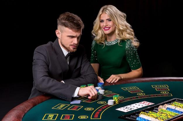 Weergave van jonge, zelfverzekerde man met de dame terwijl hij pokerspel speelt. de blondine kijkt in de camera en lacht