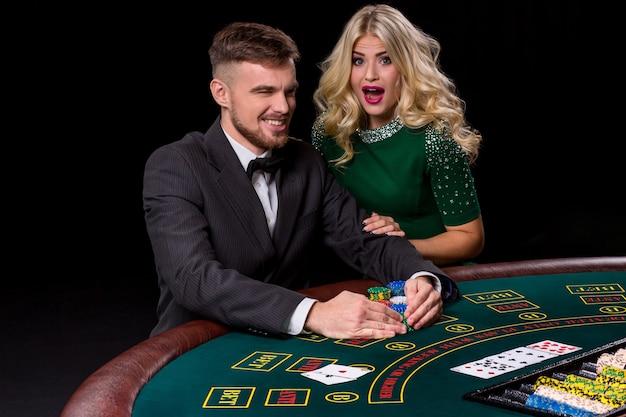 Weergave van jonge, zelfverzekerde man met de dame terwijl hij pokerspel speelt. de blondine kijkt in de camera
