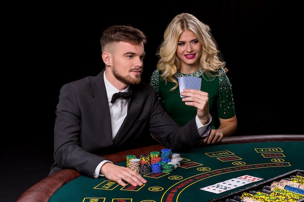 Weergave van jonge, zelfverzekerde man met de dame terwijl hij pokerspel speelt. man zet in op poker