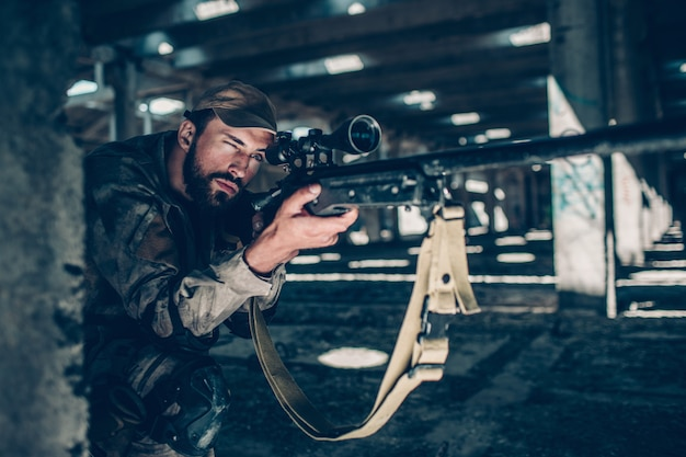 Weergave van krijger zitten dicht bij de grond en wachten. hij richt zijn doel door door de lens op zijn geweer te kijken. guy is erg geconcentreerd. hij let op.