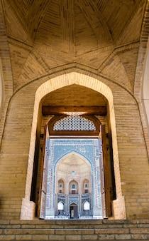 Weergave van mir-i arab madrasa door de deuropening van de kalyan-moskee in bukhara, oezbekistan. unesco-erfgoed