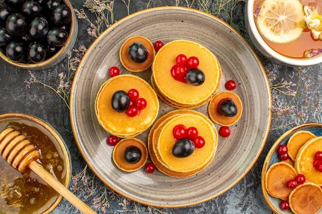 Weergave van ontbijt met stapel pannenkoeken kopje thee met citroen en honing zwarte kers sluit