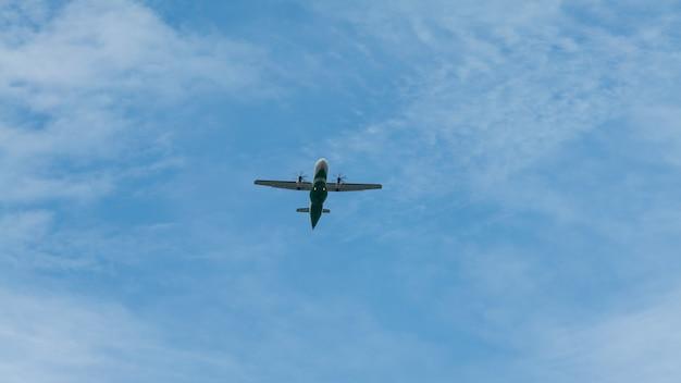 Weergave van propellervliegtuig vliegt laag met blauwe lucht en wolken op de achtergrond. commerciële passagiersvliegtuigen die over het hoofd vliegen. vliegtuig in de lucht. vliegreis