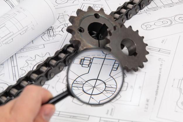 Weergave van technische tekeningen en kettingwiel voor het aandrijven van industriële rollenkettingen door een vergrootglas