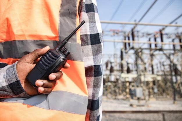 Weergave van terug engineering man met behulp van walkie talkie en veiligheidshelm dragen voor high power power plant. achteraanzicht van aannemer op achtergrond van moderne gebouwen.