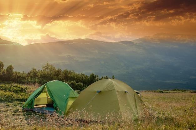 Weergave van toeristische tent in bergen bij zonsopgang of zonsondergang. camping achtergrond. avontuurlijke reizen actieve levensstijl vrijheid concept. zomervakantie.