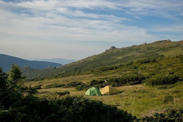 Weergave van toeristische tent in bergen bij zonsopgang of zonsondergang. camping. avontuurlijke reizen actieve levensstijl vrijheid concept. zomervakantie.