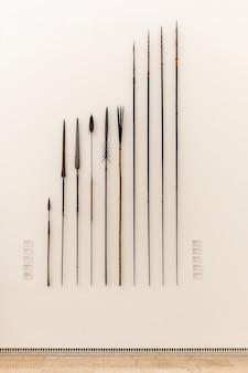 Weergave van verschillende oude speren in een museum op een witte muur.