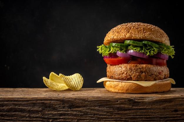 Weergave van verse smakelijke hamburger op houten rustieke tafel.