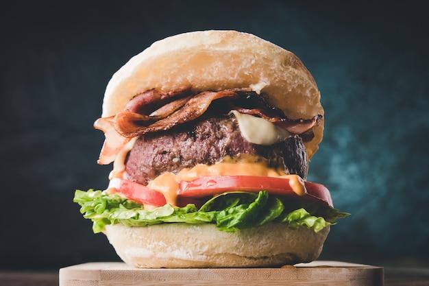 Weergave van verse smakelijke hamburger op houten tafel. hamburger met spek, kaas, sla, tomaat en saus