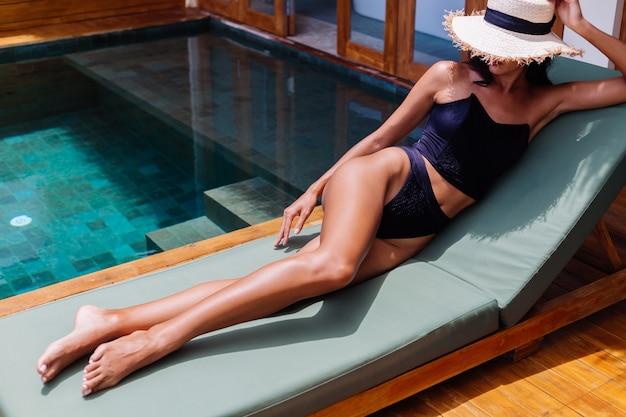 Weergave van vrij gebruinde vrouw in zwarte vintage bikini ligt op groene zonnebank in geweldige villa op zonnige dag, rusten, genieten van vakantie