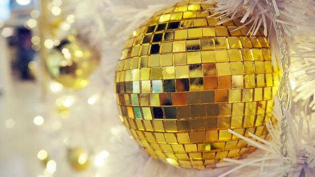Weerspiegelde discobal en kerstmisdecoratie op een witte achtergrond.