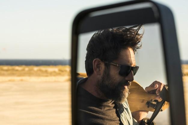 Weerspiegelde weergave van bebaarde man met skateboard in autospiegel. volwassen man met zonnebril die buiten de auto staat terwijl hij lonboard vasthoudt.