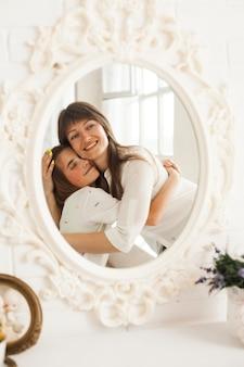 Weerspiegeling die van glimlachende moeder haar dochter omhelst