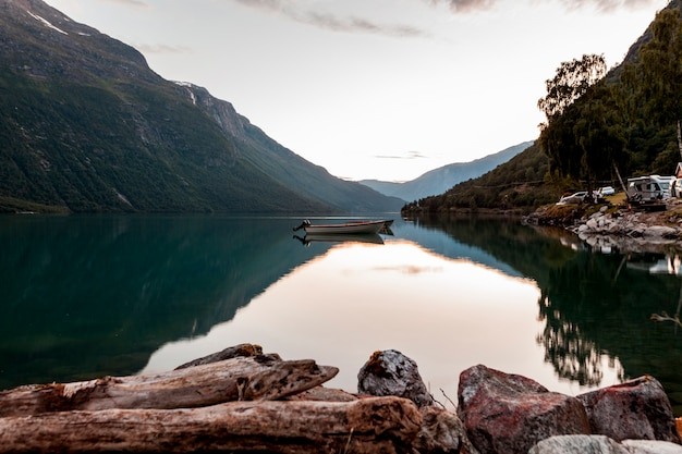 Weerspiegeling van berg en boot op kalm meer