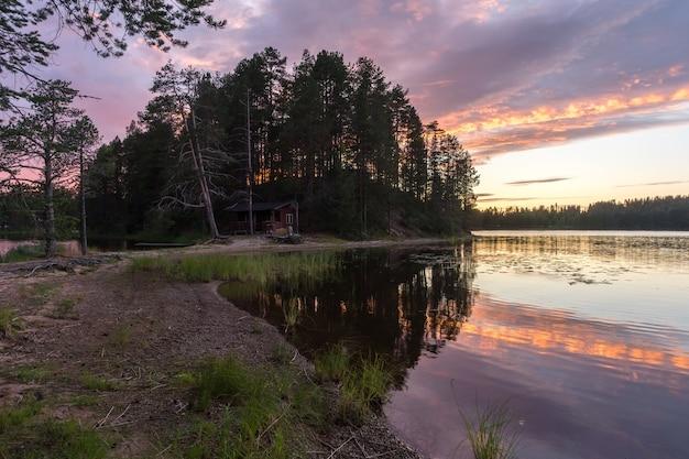 Weerspiegeling van bomen bij kleurrijke zonsondergang in het meer