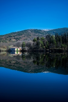 Weerspiegeling van bomen en heuvels op een meer onder het zonlicht en een blauwe hemel