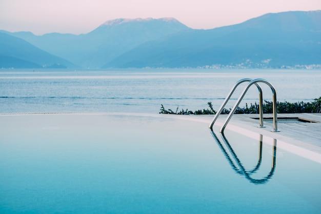 Weerspiegeling van de avondlucht in het gladde water van het zwembad bij de zee tegen de achtergrond van