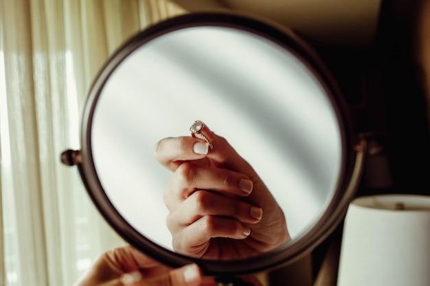 Weerspiegeling van de hand van de woma met verlovingsring in een spiegel