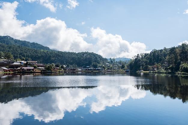 Weerspiegeling van de hemel van het kleine stuwmeer in het landelijke dorp.