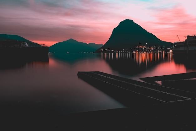 Weerspiegeling van de lichten en de berg in een meer gevangen in parco ciani, lugano, zwitserland
