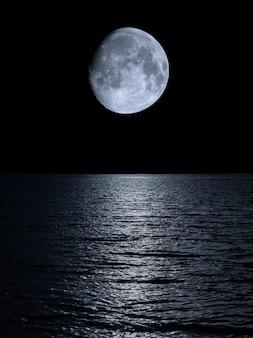 Weerspiegeling van de maan boven de kalme zee