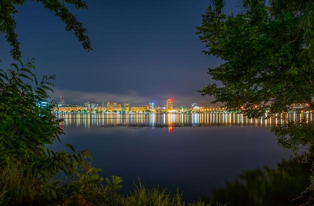 Weerspiegeling van de nachtstad in een brede kalme rivier.
