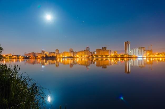 Weerspiegeling van de nachtstad op de waterspiegel