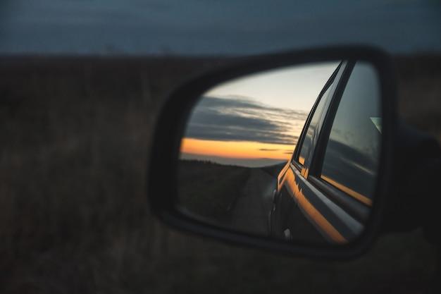 Weerspiegeling van de prachtige zonsondergang door de buitenspiegel van de auto
