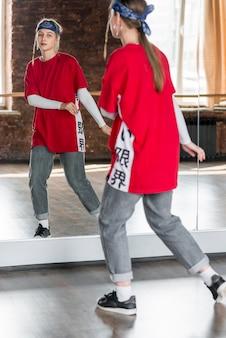 Weerspiegeling van een jonge vrouw die in de studio danst