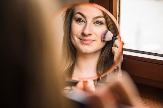 Weerspiegeling van een mooie vrouw die make-up op haar gezicht doet