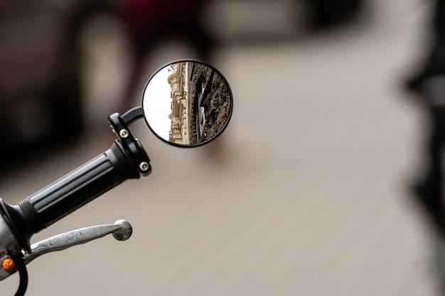 Weerspiegeling van een oud residentieel gebouw in de achteruitkijkspiegel van een motorfiets voor een vaag trottoir