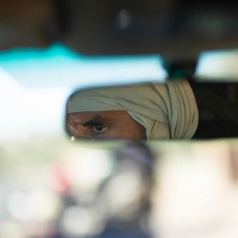 Weerspiegeling van een toeareg-mens in de achteruitkijkspiegel, atlasbergen, marokko