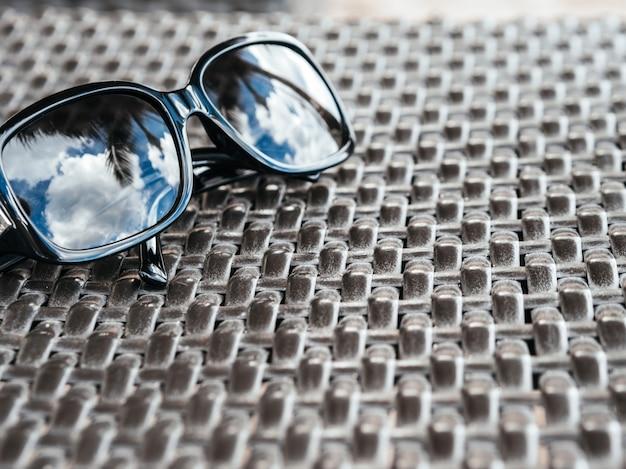 Weerspiegeling van een tropisch resort in zonnebril