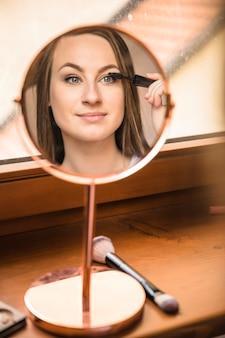 Weerspiegeling van een vrouw die mascara op wimpers toepast