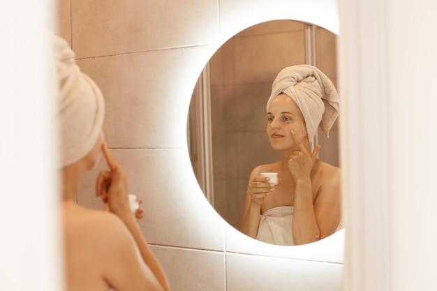 Weerspiegeling van een vrouw in de spiegel die cosmetische crème op haar gezicht wrijft, vochtinbrengende crème op haar gezichtshuid aanbrengt in de badkamer, in een witte handdoek wordt gewikkeld, schoonheidsprocedures doet.