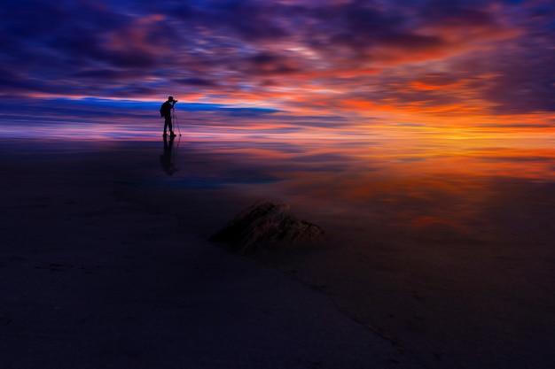 Weerspiegeling van fotograaf met verbazingwekkende hemel van tijd zonsondergang