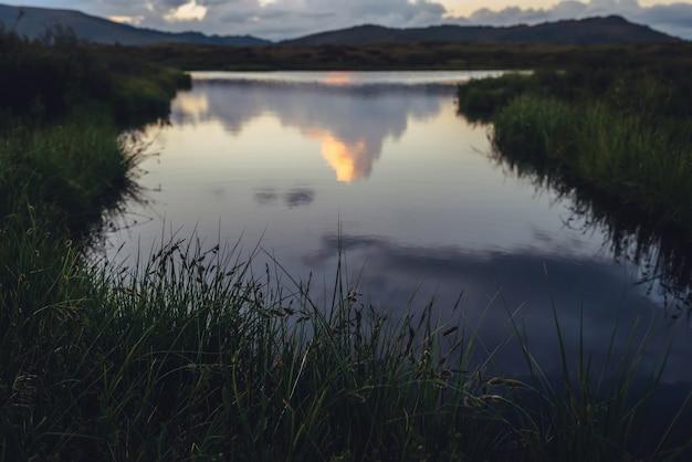 Weerspiegeling van gele grote wolk in de vorm van een explosie in het bergmeer. geweldige gigantische wolk weerspiegeld in meerwater tussen groene grassen bij zonsopgang. enorme wolk van verhelderende kleur in de hemel met dageraadgradiënt.