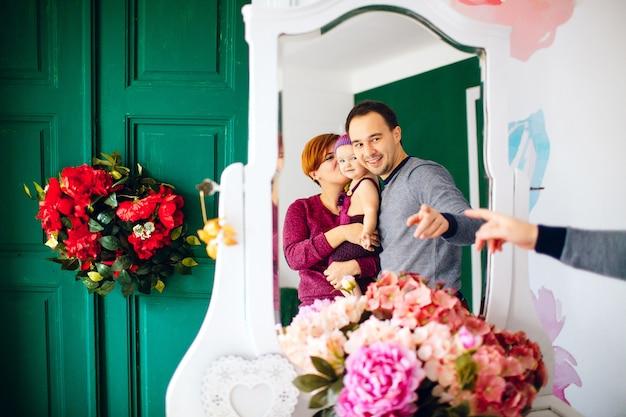Weerspiegeling van gelukkige ouders met klein meisje in witte spiegel