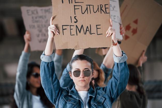 Weerspiegeling van grond in zonnebril. een groep feministische vrouwen protesteert buitenshuis voor hun rechten
