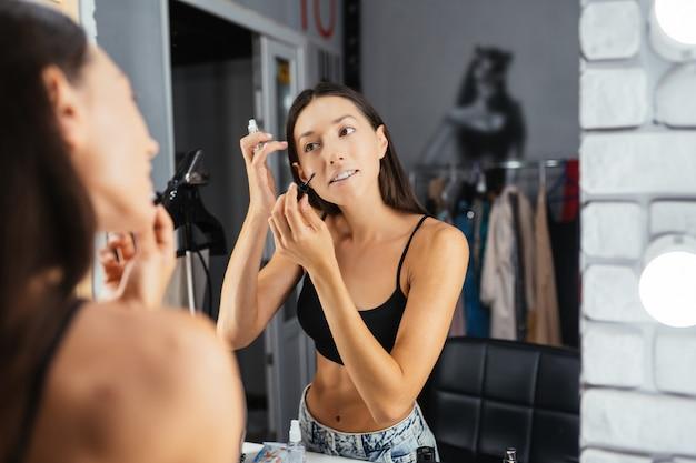 Weerspiegeling van jonge mooie vrouw die haar make-up aanbrengt, in een spiegel kijkt looking