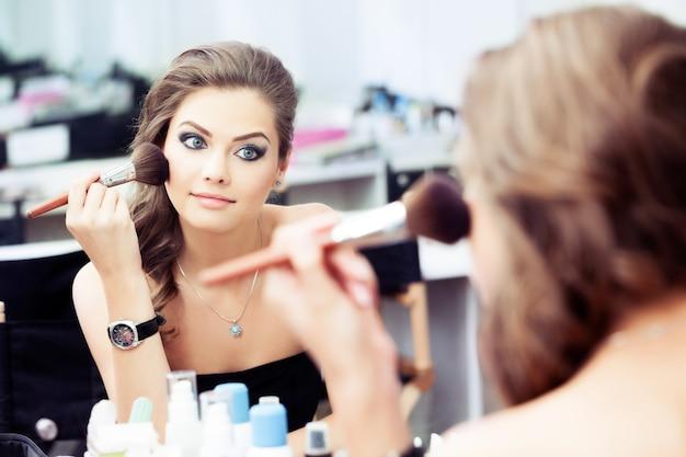 Weerspiegeling van jonge mooie vrouw die haar make-up aanbrengt